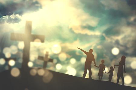 空の明るい日光の下で 3 つの十字架シンボルに向かって丘の上を歩いての家族のシルエット 写真素材