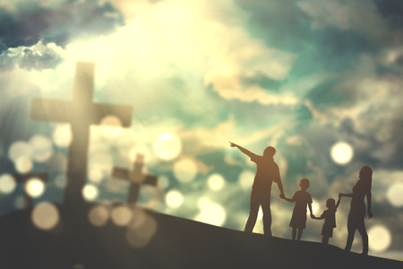 Silhouette of family walking on the hill towards three crucifix symbols with bright sunlight on the sky Imagens - 72688213