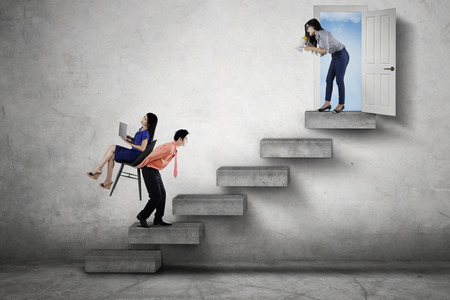 upward struggle: Picture of angry boss shouting through a megaphone while commanding her worker to walk upwards on the stairway