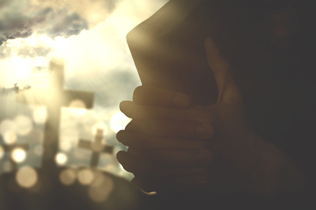 cross arms: Silhouette of human hands holding a bible and praying with a crucifix symbol and sunbeam on the sky Stock Photo