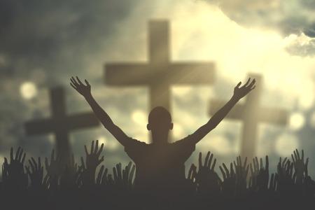 el cielo: Silueta de oraciones cristianas que levanta la mano mientras que ruega al dios con tres símbolos cruzados