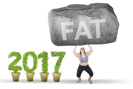 Young woman lifting a big stone with a fat word and wearing sportswear near number 2017, isolated on white background
