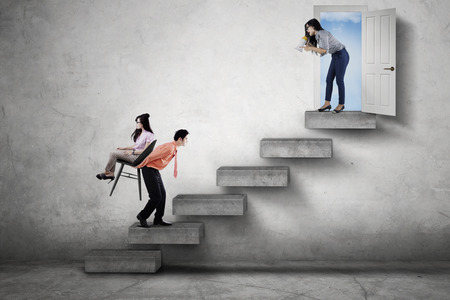 upward struggle: Female boss yelling through a megaphone while commanding her employees to walk upward on the stair