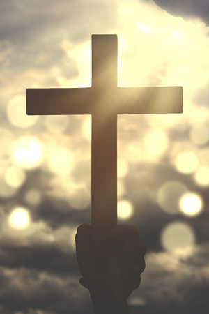 Silhouette of human arm holding a christian crucifix symbol with defocused sunlight on the sky
