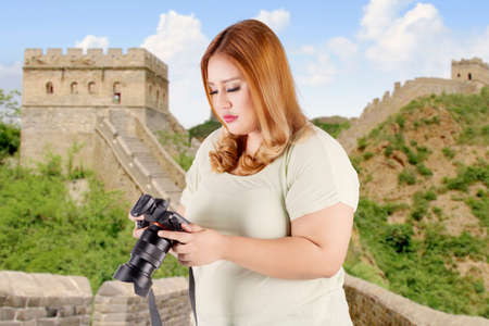 foreign bodies: Image of female photographer standing on the Great wall of China while viewing photos on the digital camera Stock Photo