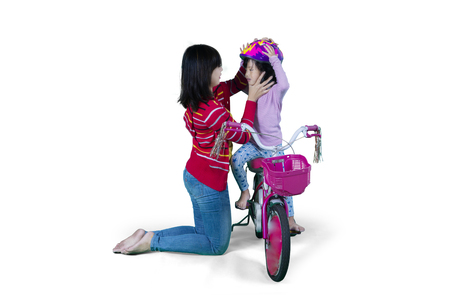fastens: Portrait of young mother fastens a helmet to her daughter while riding on the bicycle