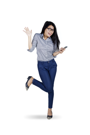 asia women: Full length of Asian businesswoman looking at the camera and holding a mobile phone while celebrating her success on studio Stock Photo