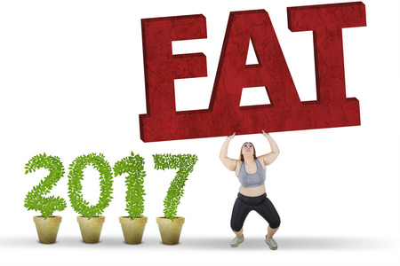 chinese lady: Overweight woman lifts a fat word while wearing sportswear near number 2017, isolated on white background