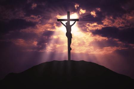 Afbeelding van een christelijk kruis op de heuvel met zonnestraal in de lucht bij zonsopgangstijd