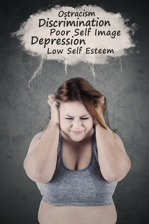 low self esteem: Portrait of stressful overweight woman thinks her problems while scratching her head Stock Photo