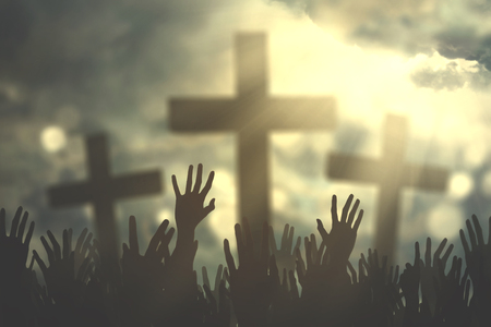 Group of christian people hands praying together with three cross symbol and bright sunbeam on the sky
