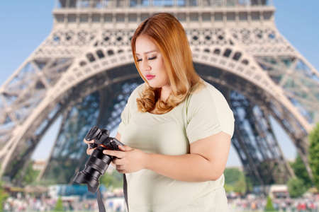 viewing: Portrait of female tourist is standing near the Eiffel tower while viewing photos on the digital camera