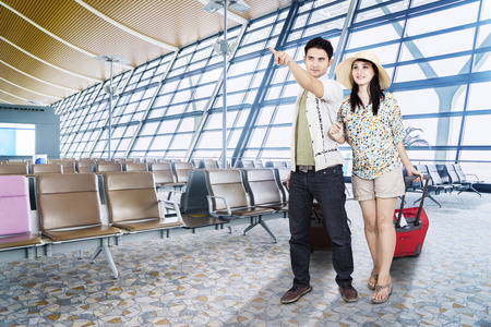 luggage travel: Image of young couple is pointing flight information on the board while walking in the airport terminal Stock Photo