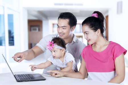 study: Portrait of happy parents teaching daughter by using laptop while sitting at home