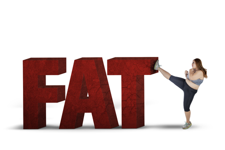 health care fight: Overweight woman kicking word of fat in the studio, isolated on white background