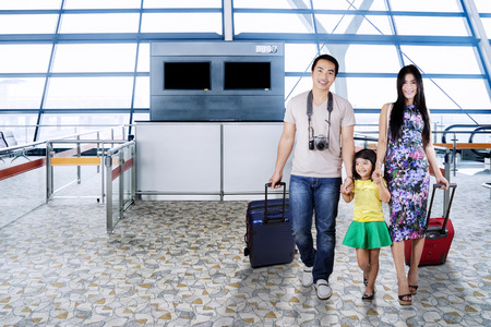 Young Asian family carrying suitcase and smiling at the camera while entering into the airport termina