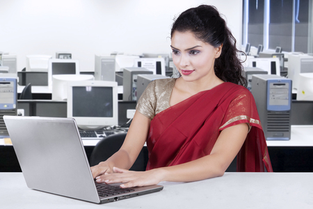 Indian young woman working with notebook computer in the office while wearing traditional clothes