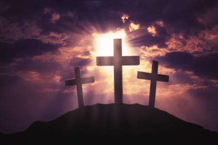 Wizerunek trzy chrześcijańskiego krzyża symbolu na wzgórzu z jaskrawym światłem słonecznym na niebie przy zmierzchu czasem