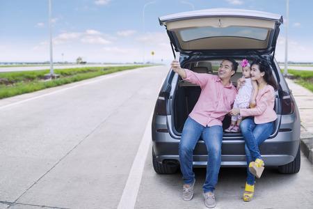 Gelukkig gezin zitten achter de auto, terwijl het nemen van selfie foto met behulp van smartphone op de straat