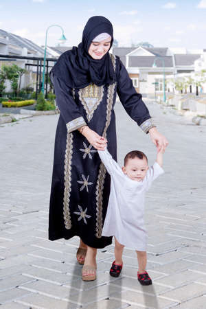 Image of young Arabian mother is teaching her cute boy to learn first step on the road Stock Photo