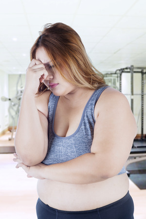 low self esteem: Portrait of overweight woman standing in the fitness center and looks stressful