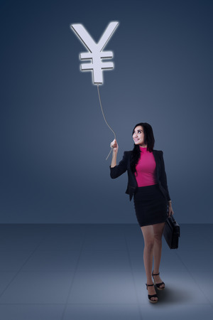 Businesswoman standing while looking yen symbol over her head Stock Photo