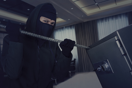 thievery: Male thief wearing a mask and trying to open a safe-deposit box in the office