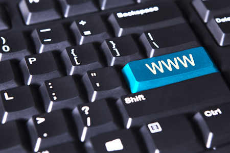 domains: Close up of blue www button on black keyboard background Stock Photo