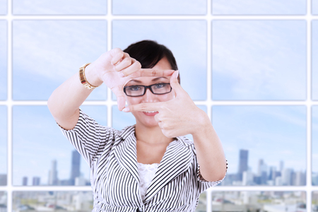 modern businesswoman: Asian businesswoman creating frame with fingers at modern office Stock Photo