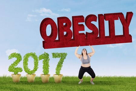 Overweight woman lifting obesity word while wearing sportswear near number 2017, shot outdoors