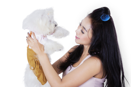 Image of beautiful woman is holding and smiling with her Maltese dog in the studio Stock Photo