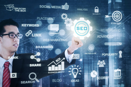 Young Asian businessman wearing formal suit and pressing a virtual SEO icon. SEO concept photo