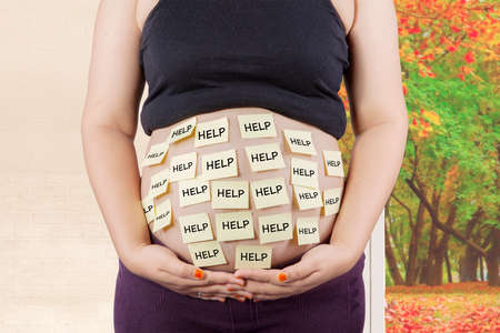home birth: Pregnant woman holding her belly with help text while standing at home, autumn background on the window