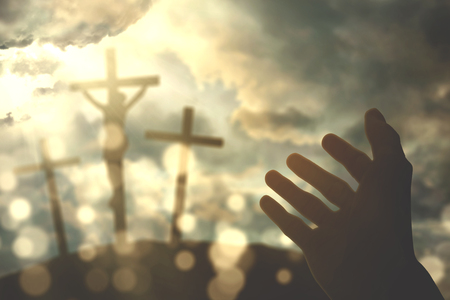 Hands of a Christian man while praying to god with three crucifixes at sunrise in the hill