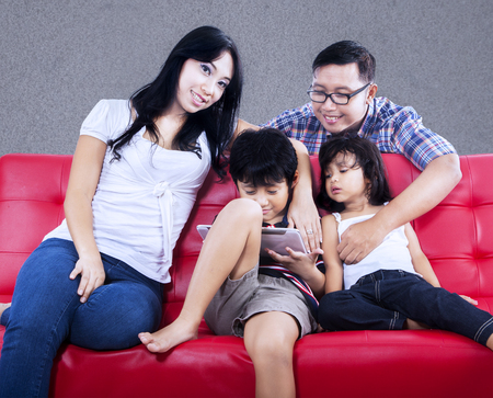 red sofa: Happy Asian family enjoy relaxing time on red sofa with grey background Stock Photo
