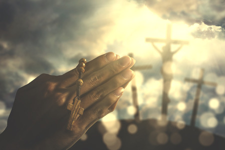 Hands of a Christian man holding a rosary while praying to god with three crucifixes under sunbeam in the hill Stock Photo