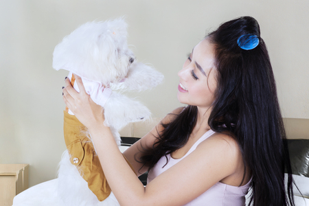 Picture of pretty young woman is holding and smiling with her Maltese dog while sitting on the bedroom Stock Photo
