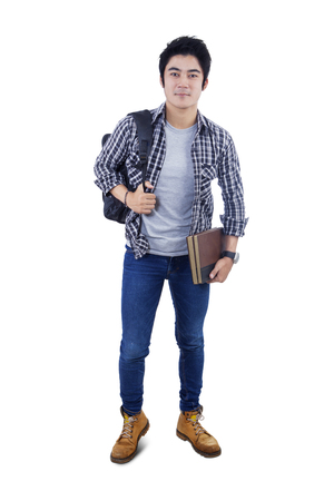 teenage male: Full length of male student carrying backpack and books while standing in the studio Stock Photo