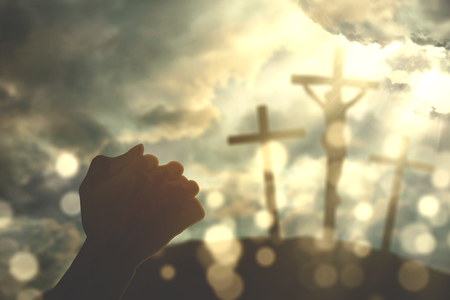 Closeup of hands folded while praying to God with three crucifixes under sunbeam Stock Photo