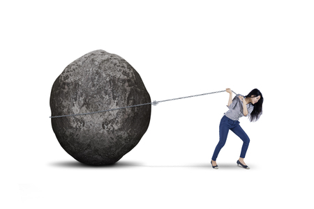 Young female entrepreneur is pulling big stone with a chain, isolated on white background
