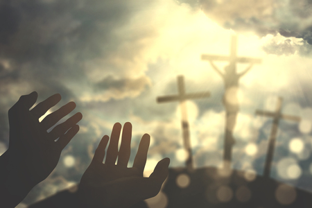Image of hands praying to the God with three crucifixes under sunbeam in the hill Stock Photo