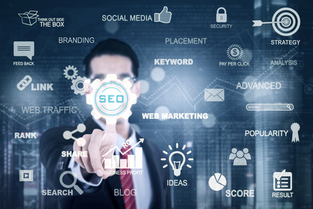 Picture of a young businessman touching a virtual SEO button on the futuristic screen. SEO concept photo