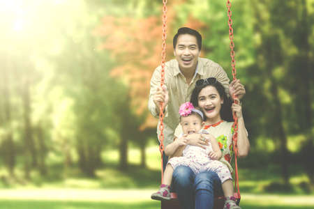 fun activity: Cheerful Asian family playing on a swing at the park, shot at summer time