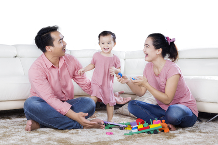 Image of cheerful family playing with toys while sitting on the carpet, isolated on white background Stock Photo