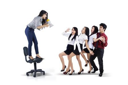 Foto de la joven líder gritando a su trabajo en equipo mediante el uso de un megáfono, aislado en fondo blanco