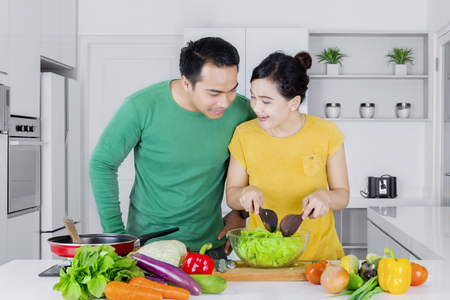 young wife: Portrait of a young man looking his wife making vegetables salad in the kitchen