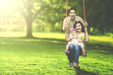 family together: Portrait of a joyful family laughing together while playing on a swing at the park