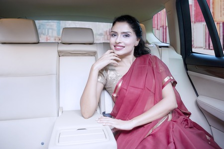 exporter: Successful Indian businesswoman wearing saree clothes while smiling inside car with container on the background. Concept of successful importer or exporter Stock Photo