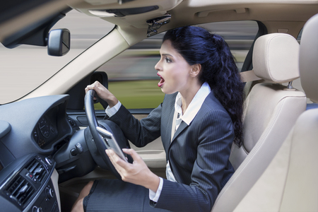 photo: Photo of a female worker driving a car while using her smartphone and looks shocked at the road