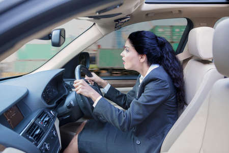 exporter: Photo of a shocked Indian businesswoman driving a car while looking at the road